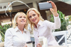 Elegant mother and daughter taking shot on smartphone stock photo