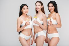 Elegant multicultural girls holding glasses with lemon water. Isolated on grey healthy lifestyle stock images