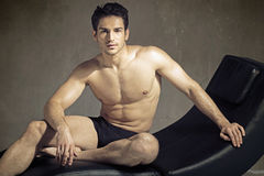 Elegant muscular guy in fashion pose Stock Photography