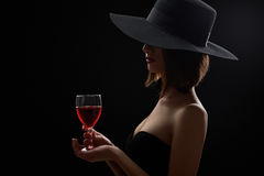 Elegant mysterious woman in a hat holding a glass of red wine on Stock Photo