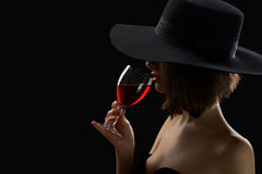 Elegant Mysterious Woman In A Hat Holding A Glass Of Red Wine On Royalty Free Stock Images