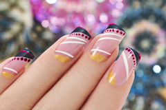 Elegant nail design. Elegant nail design on a rectangular shape nails covered with light pink lacquer with black, white,Golden figure Stock Photography