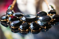 Elegant necklace with black stones and a Golden metal base on a reflective black mirror surface. Dark precious stones in the form. Of droplets and ovals stock photos