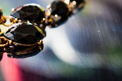 Elegant necklace with black stones and a Golden metal base on a reflective black mirror surface. Dark precious stones in the form. Of droplets and ovals stock image