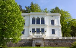 Elegant Neoclassic Building at Lake Bled. BLED, Slovenia - April 25, 2018: Elegant neoclassic building surrounded by a beautiful park just over the lake Stock Image