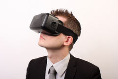 Elegant, neutral man in a black formal suit, wearing a VR Virtual reality Oculus Rift 3D headset, looking upwards to the left Royalty Free Stock Image