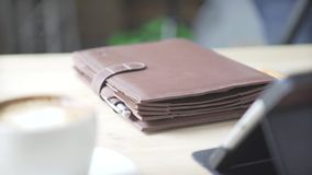Elegant note pad book bullet journal habit tracker in light brown leather case holder on wooden table with tablet. Close up shot of elegant light brown leather stock footage
