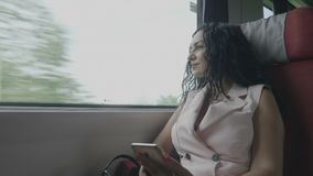Elegant office woman in train commuting from work resting during his travel back to home enjoying listening music on smartphone -. Elegant office woman in train stock video