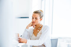 Elegant office worker. Attractive young woman sitting at desk and using her mobile phone Royalty Free Stock Image