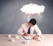 Stressed out businessman at office desk. An elegant office worker is having a bad day while working, illustrated by a white cloud above his head with heavy rain Stock Photos