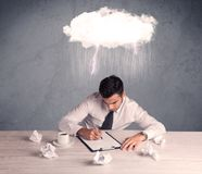 Stressed out businessman at office desk. An elegant office worker is having a bad day while working, illustrated by a white cloud above his head with heavy rain Stock Photo