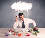 Stressed out businessman at office desk. An elegant office worker is having a bad day while working, illustrated by a white cloud above his head with heavy rain Royalty Free Stock Photos