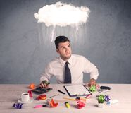 Stressed out businessman at office desk. An elegant office worker is having a bad day while working, illustrated by a white cloud above his head with heavy rain Stock Photography