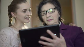 Elegant old business woman and young girl using a tablet on the room background stock video