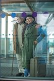 Elegant old woman and man are waiting for flight. Our first trip. Full length of pleasant aged couple is standing together at airport building with suitcase Royalty Free Stock Photo