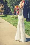 Elegant omslag för ` s för brudinnehavbrudgum över hennes skuldra fotografering för bildbyråer