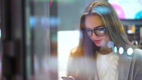 Elegant onderneemster het draaien telefoonaantal en het uitnodigen van smartphone 4K jonge mooie vrouw die een mobiele telefoon b stock video