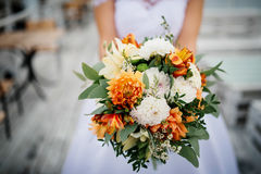 Elegant orange and white wedding bouquet at hands of bride.  Royalty Free Stock Images