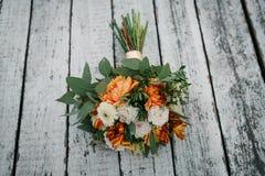 Elegant orange and white wedding bouquet on wooden background.  Stock Photography