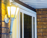 Elegant ornate porch light glowing by front door, welcoming Stock Photo