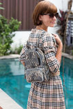 Elegant outfit. Close up of stylish luxury snakeskin python backpack in woman hand. Female fashion concept. Elegant outfit. Close up of stylish luxury snakeskin Royalty Free Stock Images