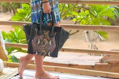 Elegant outfit. Closeup of snakeskin python bag handbag in hand of stylish woman fashionable girl outside. Female Stock Photography