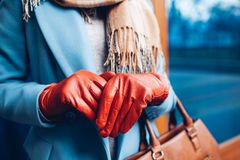 Elegant outfit. Closeup of of stylish woman in coat, scarf and brown gloves. Fashionable girl on the street. royalty free stock photo