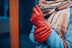 Elegant outfit. Closeup of of stylish woman in coat, scarf and brown gloves. Fashionable girl on the street. royalty free stock images