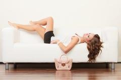 Fashionable girl with handbag lying on sofa Royalty Free Stock Image