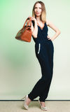Elegant outfit. Stylish woman with brown bag Stock Images
