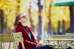 Elegant Parisian woman drinking coffee in park Royalty Free Stock Images