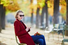 Elegant Parisian woman drinking coffee in park Stock Images