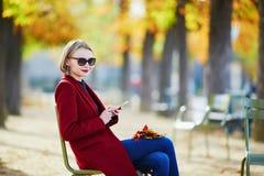 Elegant Parisian woman using her mobile phone in park stock image
