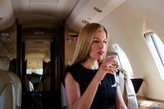 Elegant passenger on plane drinking wine Stock Images
