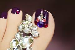 Elegant pedicure with rhinestones. Elegant pedicure with rhinestones on purple nail varnish female foot on a dark background stock images