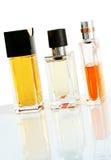Elegant perfume bottles. Three elegant perfume bottles standing on reflective surface royalty free stock image