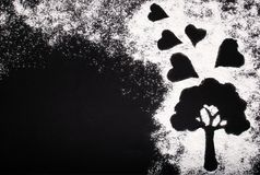 Elegant picture of white wheat flour and a tree with hearts on a black background royalty free stock photography