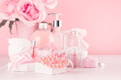 Elegant pink skin and body care products - cream, rose oil, liquid soap, salt, cotton towel - cosmetic accessories, flower.