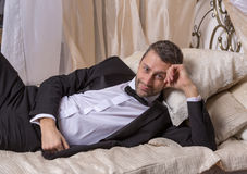 Elegant playboy reclining on a bed. Elegant handsome playboy in a bow tie and suit reclining on a bed in an elaborate bedroom with a seductive smile on his face Stock Images