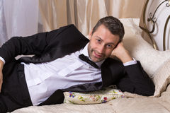 Elegant playboy reclining on a bed. Elegant handsome playboy in a bow tie and suit reclining on a bed in an elaborate bedroom with a seductive smile on his face Royalty Free Stock Images