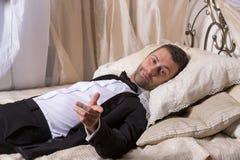 Elegant playboy som vilar på en säng arkivbilder