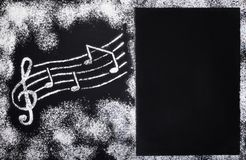 Elegant postcard on the theme of baking with pictures of musical notes made of white wheat flour on a contrasting black background royalty free stock photography