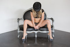 Elegant and pretty blond woman sitting on a sofa Stock Photo