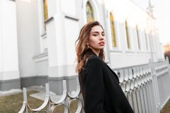 Elegant pretty modern young woman in a stylish black coat walking down the street near a gray fence. On the background of a vintage building. European girl stock photos