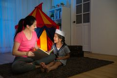 Elegant pretty mother holding history book. Talking with little girl discussing adventure route plan when her daughter dress up sailor and playing game at night Royalty Free Stock Photography