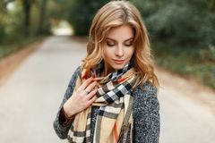 Elegant pretty sweet young woman with blond hair in a vintage gray coat with a stylish beige warm scarf standing on the road. In the park. Modern attractive royalty free stock image