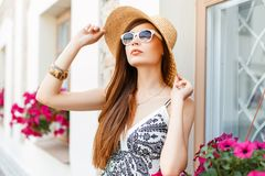 Elegant pretty woman in a beach hat and sunglasses standing. Near a vintage building, looking up royalty free stock image