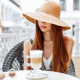 Elegant pretty woman with red lips in a hat is sitting. At a table in a summer cafe. On the table is a coffee and sunglasses stock photo