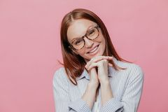 Elegant pretty woman tilts head, keeps hands under chin, wears transparent glasses and shirt, smiles gently, models over pink stock photo