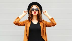 Elegant pretty woman wearing a black hat, sunglasses and jacket. Over urban grey background stock photos